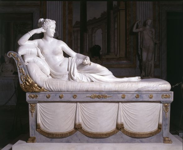 A sculpture. A woman half-nude, with a cloth covering the lower half of her body. She partially reclines on a bed with pillows supporting her. The bed is ornately carved of a blue-grey stone and gilded with gold.