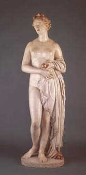 A nude woman standing upright, her arms folded in front of her. She holds a golden apple in her left hand. There is a swath of fabric folded over her left arm, draping to the ground, partially covering her lower body.