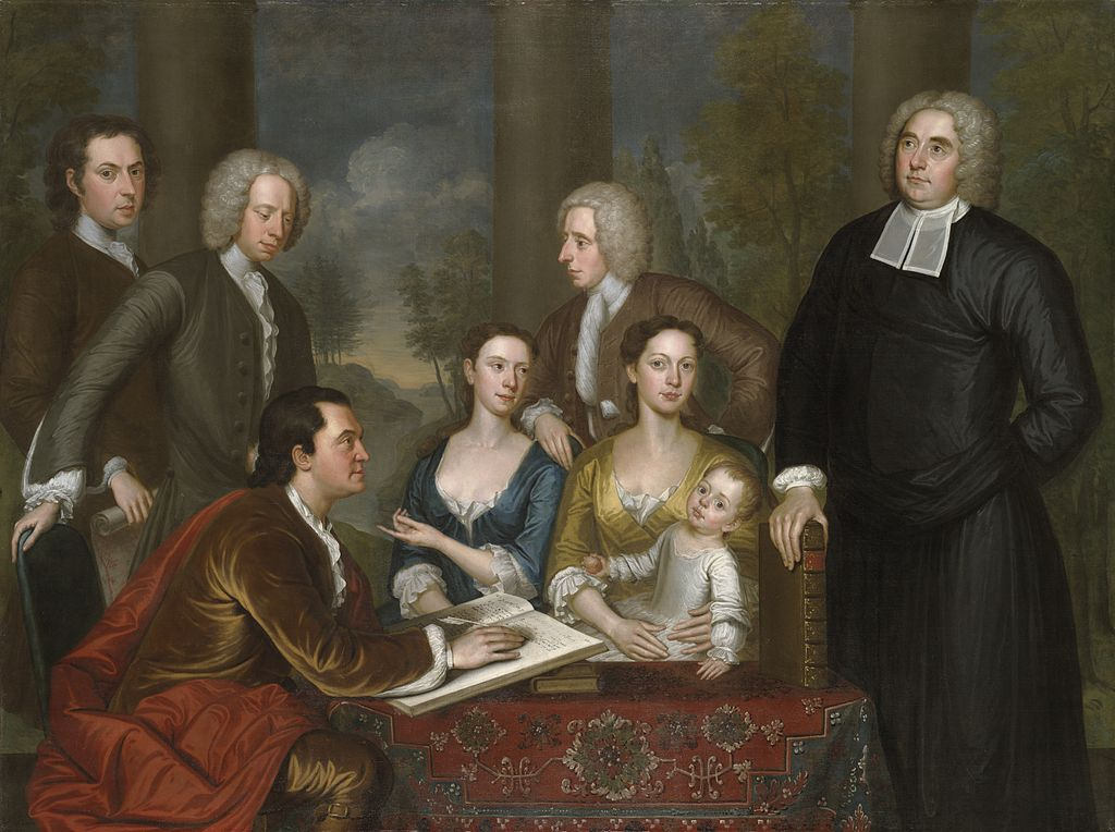 A man and two women sit at a table, one of the women has a baby on her lap. Four men stand behind the group. The table has a rich red tablecloth and the man at the table is dressed in velvet, with a red wrap.