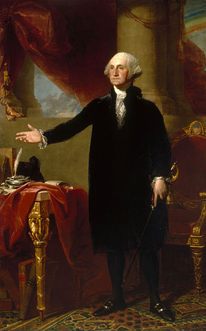 A full portrait of George Washington. He stands with his feet shoulder-width apart, with his right hand extended in an open gesture. His clothes are a plain black and white, but the room behind him is more richly garbed in reds and golds. The exposed leg of a table at George's side is exquisitely carved, with eagle details clearly prominent.