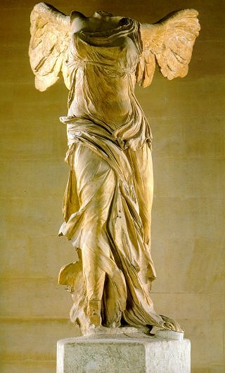 A marble sculpture of a winged woman. Over time, her head and arms have been lost. Her draping clothes appear light and flowing, despite the hard medium of the sculpture.