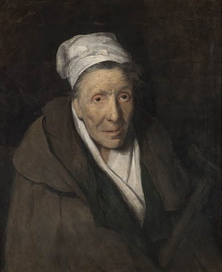 An elderly woman with a white cloth covering her hair. She wears a heavy brown coat over white clothes. The coat seems old and too large for the woman.