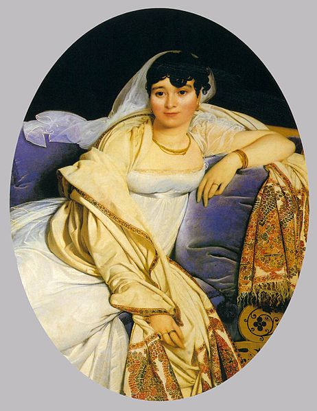 A woman relaxing on a cushioned chair. The cushion is a rich blue. The woman is wearing a white dress with a cream shawl over her arm.