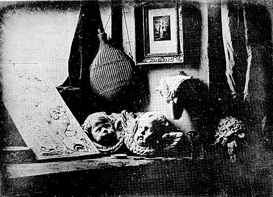 a black and white daguerreotype featuring a window, two sculpted cupid heads, a flask, and a painting.