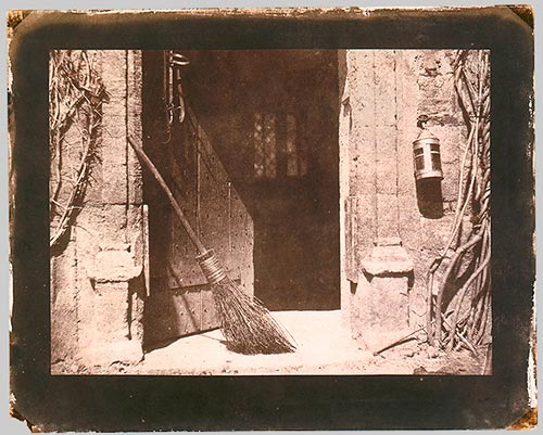 An open doorway with a broom leaning on one side of the frame. A lantern hangs by the other side of the door.