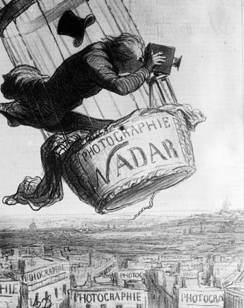 Nadar in a hot air balloon, taking photographs of the city below. His hat has flown off his head, and he looks precariously balanced.