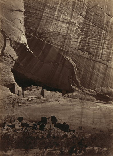 Ancient ruins in front of a vast canyon wall. The ruins are dwarfed by the scope of the wall's size.