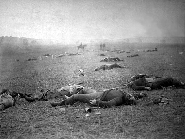 One soldier's body lies at the center of the photograph. A few dozen other men can be seen scattered across the ground. In the background of the photo, a man on horseback sits in the middle of the scene.