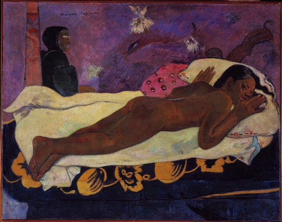 A young Tahitian woman lies on nude on her stomach on a bed. She looks out to the viewer of the painting.
