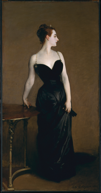 A full body portrait. A woman stands, wearing a floor length black dress with a sweetheart neckline and jeweled straps. She looks away from the viewer, with her face in profile.