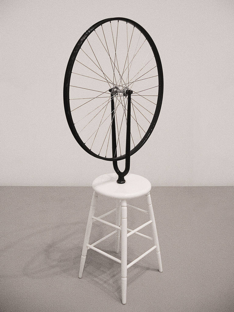 A white four-legged stool with a bike wheel affixed to the center of the seat. The wheel is upright.