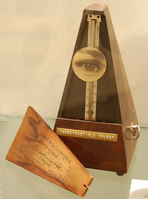 A metronome with a circular photograph of an eye and an eyebrow attached to its pendulum. The front of the metronome has a label stamped into metal: Indestructible Object.