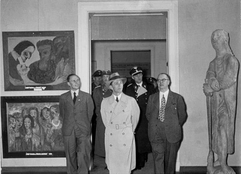 Dr. Goebbels and a group, including a security team, walk through the exhibit.