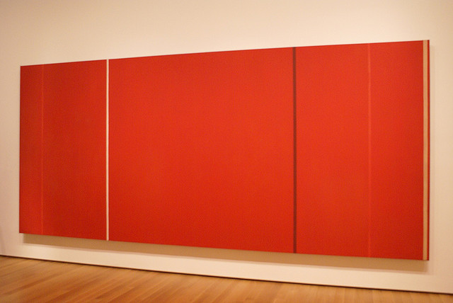 A large red rectangular canvas that is approximately twice as long as it is tall. There are three thin stripes, all of which run from top to bottom. The first white line appearing near the one-third mark of the painting, the second black line appearing near the two-third mark of the painting, and the last yellow line appearing near the very right edge of painting.