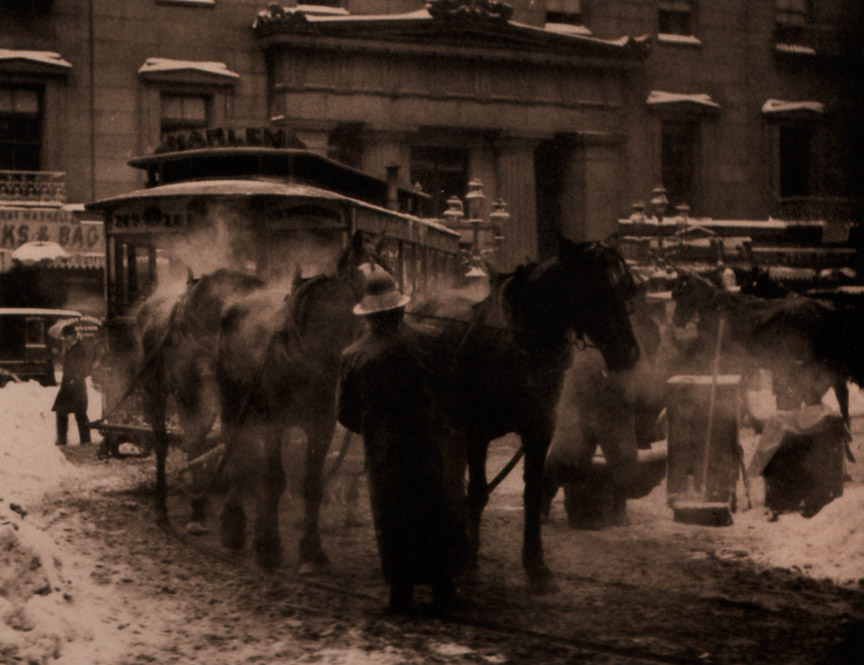 This sepia photograph of a street features horse-drawn transportation as its focal point. A man stands in front of the two horses tending to them. The ground is covered in a thin layer of dirty snow, with drifts of cleaner snow piled along the sides of the road. Hot air is visible as mist coming from the horses' mouths and bodies.