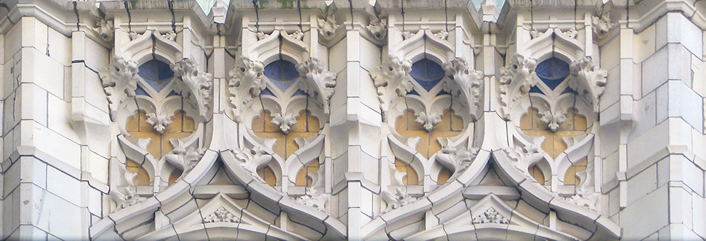 The face of the building is primarily white, with intricate swoops, curls, and fleur de lis. These swooping carvings expose blue and yellow beneath them.