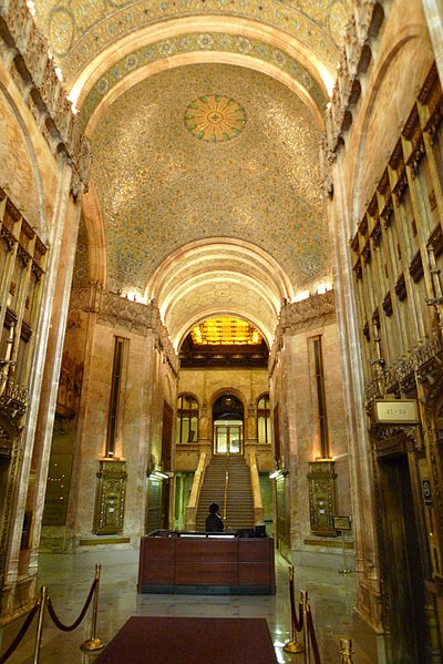 The lobby has a vaulted ceiling, two or three stories high. The floors are polished stone, the walls are carved marble, and the ceiling is gilded with intricate gold and aqua geometrical designs.