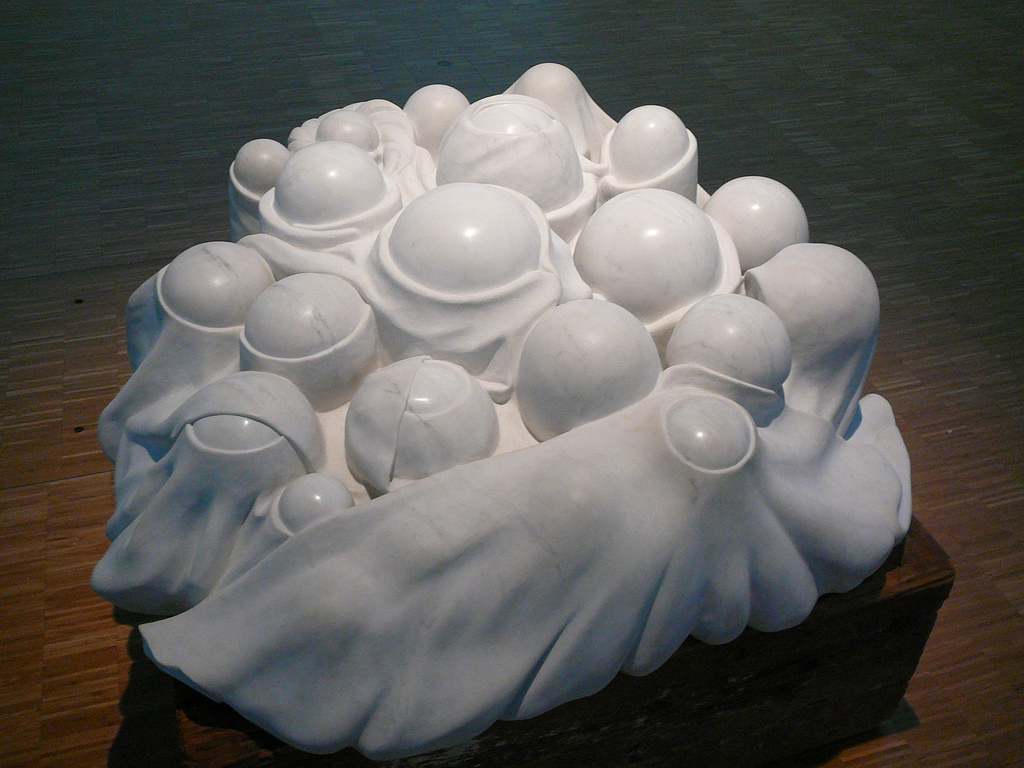A marble sculpture seen at an angle from above. There are several spherical protrusions rising from a vaguely circular base. These protrusions are different sizes and rise to different heights, but are fairly uniformly round. It appears as though a sheet (also carved from the marble) has been draped over them, but the sheet has holes, exposing the tops of each sphere. There are several layers of the sheeting.
