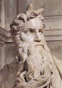 A close up of Moses's face. This picture focuses on his expression. His mouth is almost pulled into a frown, and his eyes are clearly focused on something the viewer doesn't know about.