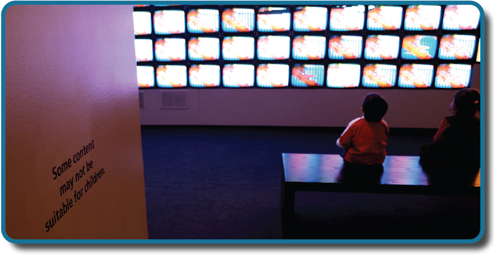 """Children sit in front of a bank of television screens. A sign on the wall says, """"Some content may not be suitable for children."""""""