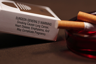 "A photograph shows pack of cigarettes and cigarettes in an ashtray. The pack of cigarettes reads, ""Surgeon general's warning: smoking causes lung cancer, heart disease, emphysema, and may complicate pregnancy."""