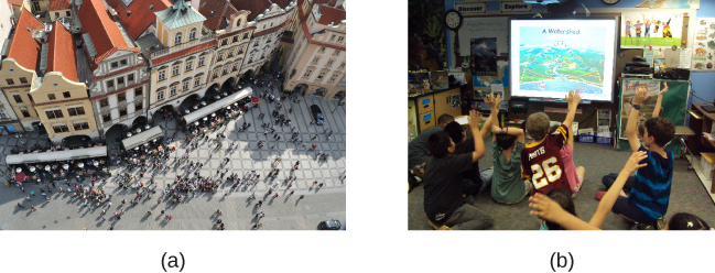 (a) A photograph shows an aerial view of crowds on a street. (b) A photograph shows s small group of children.