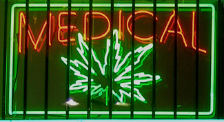 """A photograph shows a window with a neon sign. The sign includes the word """"medical"""" above the shape of a marijuana leaf."""
