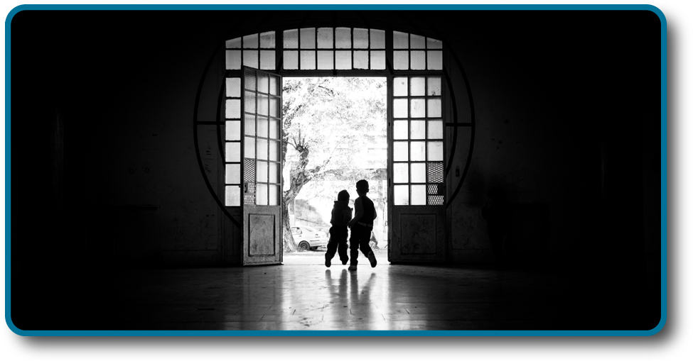 A photograph shows two children running outside through an open doorway.
