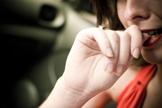 AA photograph shows a woman biting her fingernails.