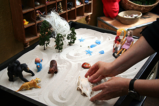 This photograph shows a person playing with objects in a small box filled with sand. The person is organizing these objects and small play figures in a form of treatment called sandplay.