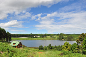 Photo looking down a hill at a lake in the distance, surrounded by one log house with a tin roof and green rolling hills and trees.  More than half the image is blue sky with streaks of white clouds.