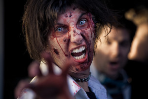 Photo of person with zombie makeup, snarling and reaching out towards the camera