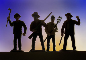 Close-up photo of four plastic figurines, in the shape of men holding axes, pitchforks, and muskets. Figures are in silhouette against a sunset backdrop