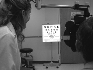 Black-and-white photo of a man looking through a lens at an eye chart. A female doctor observes.
