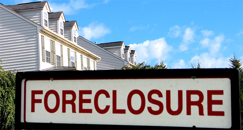 A large sign in front of a house that says Foreclosure