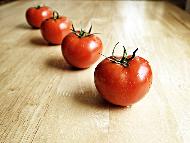 Image of four juicy, red tomatoes on a countertop.