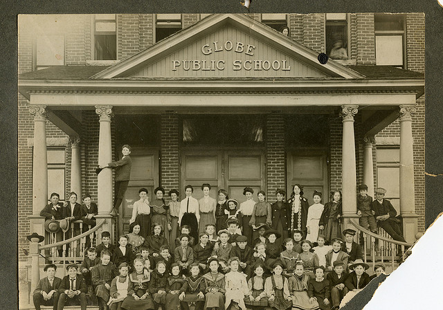Vintage, sepia-toned photograph of roughly 50 children sitting on the steps in front of the Globe Public School.