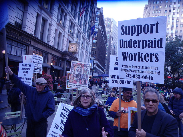 """Protestors holding placards at a NYC rally to raise the minimum wage. A sign in the forefront reads, """"Support Underpaid Workers."""""""