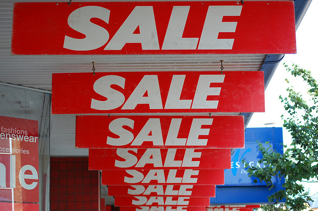 "Image of repeated, excessive ""Sale"" signs hanging outside the front of of a store."