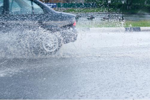 A car splashing through a puddle of rain water.