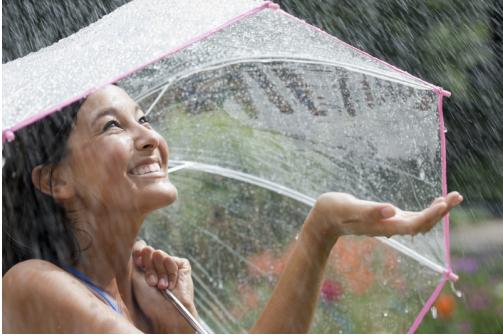 A woman standing in the rain under an umbrella.