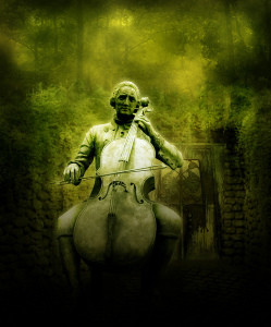 Photo of a statue: man sitting on bench, playing a cello. The photo is soft focus and green-tinted