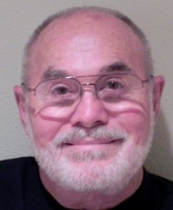 Smiling headshot of 60-year old man with white beard and glasses