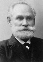 Photo of Ivan Pavlov in his older years, with a white beard, wearing a suit and tie.