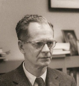 B. F. Skinner, looking away from the camera, wearing glasses and a suit and tie.