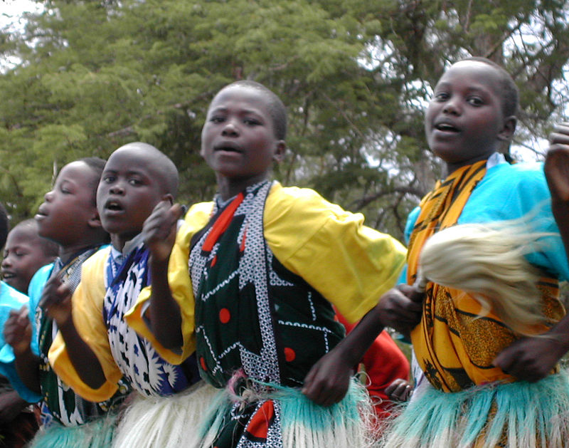 Children in their early teens wearing colorful, tribal clothing while singing and dancing.