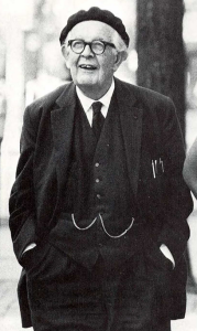 Jean Piaget standing, smiling, wearing a 3-piece suit and a beret.