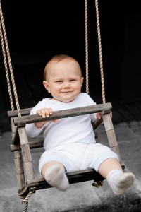 smiling baby in a swing