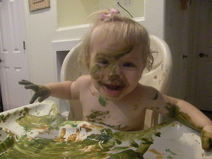 messy toddler girl covered with fingerpaint.