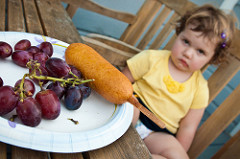 toddler girl sits behind her grapes and hotdog with a grumpy face.